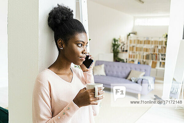 Young woman with coffee cup talking on mobile phone while standing at home