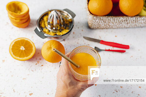 Woman holding orange juice glass with drinking straw over modern terrazzo marble
