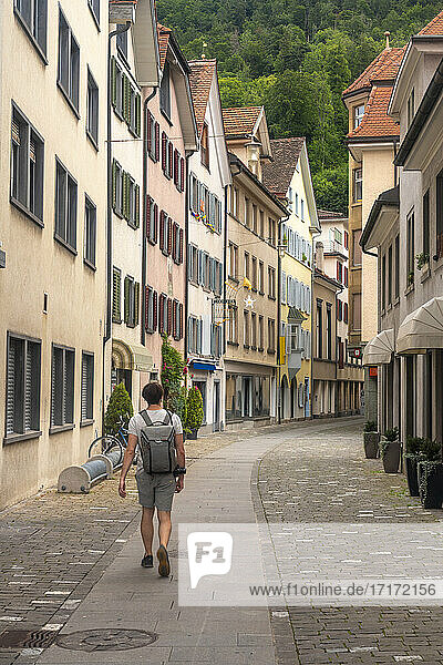 Explorer with backpack walking on Storchengasse street in old town of Chur  Switzerland