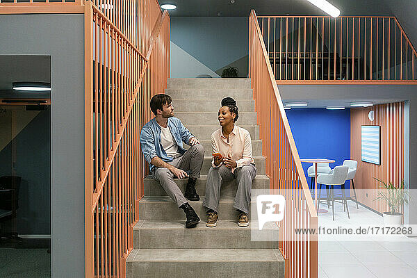 Creative male and female colleague talking while sitting on staircase at workplace