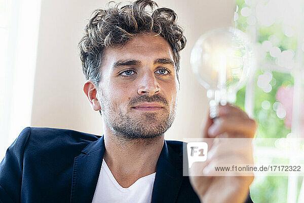 Nachdenklicher Geschäftsmann  der eine Glühbirne zu Hause hält Nachdenklicher Geschäftsmann, der eine Glühbirne zu Hause hält