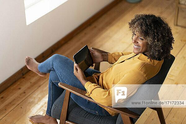 Lächelnde Frau mit digitalem Tablet  die wegschaut  während sie sich auf einem Sessel zu Hause ausruht Lächelnde Frau mit digitalem Tablet, die wegschaut, während sie sich auf einem Sessel zu Hause ausruht