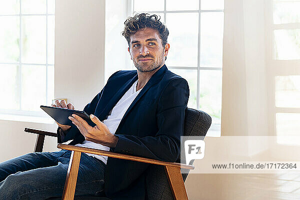 Businessman holding digital tablet while sitting on armchair at home