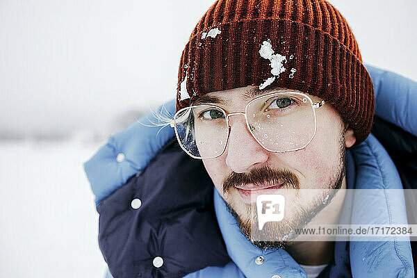 Young man with snow on knit hat during vacations