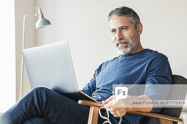 Businessman working on laptop while sitting at home