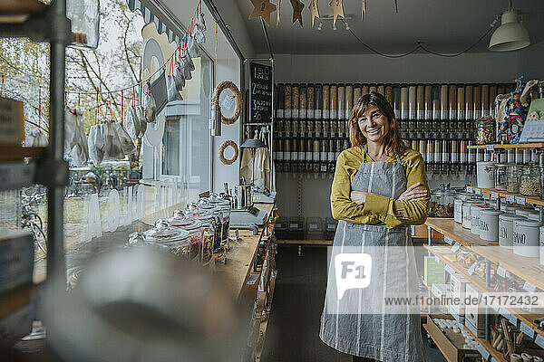 Smiling saleswoman with arms crossed standing in zero waste store