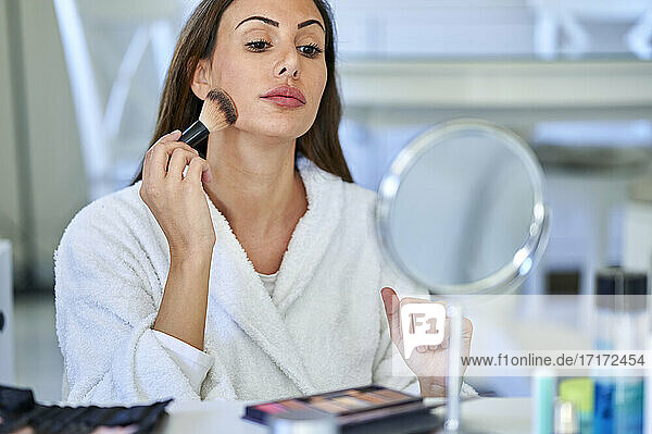 Woman applying blusher while looking in mirror at home