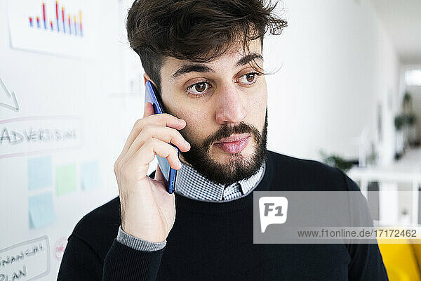 Businessman talking on phone in front of whiteboard in office