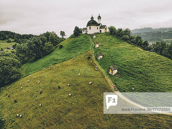 Aerial view of woman walking on green hill towards chapel against sky