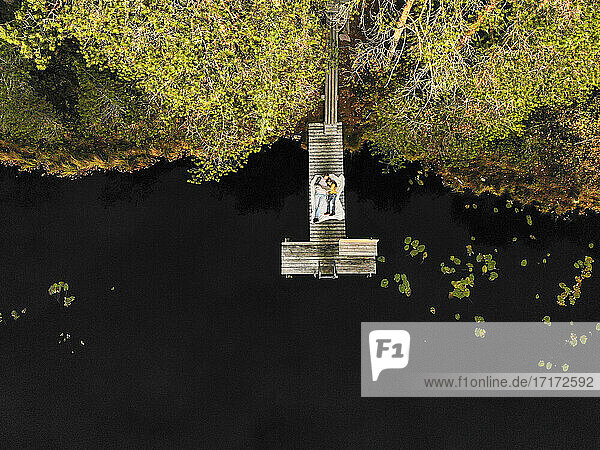 Aerial view of mother and daughter lying on pier over lake in forest