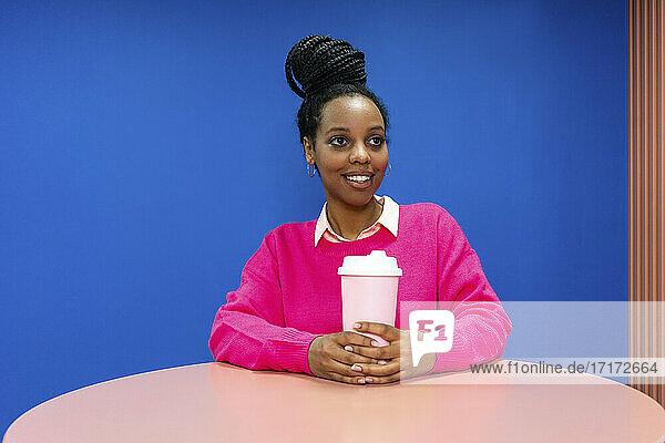 Lächelnde weibliche Fachkraft mit wiederverwendbarem Kaffeebecher träumt gegen die Wand in der Cafeteria im Büro Lächelnde weibliche Fachkraft mit wiederverwendbarem Kaffeebecher träumt gegen die Wand in der Cafeteria im Büro