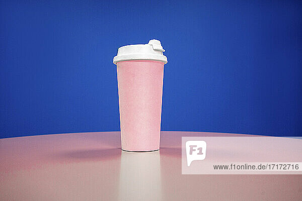Rosa wiederverwendbare Kaffeetasse auf dem Tisch vor blauem Hintergrund Rosa wiederverwendbare Kaffeetasse auf dem Tisch vor blauem Hintergrund