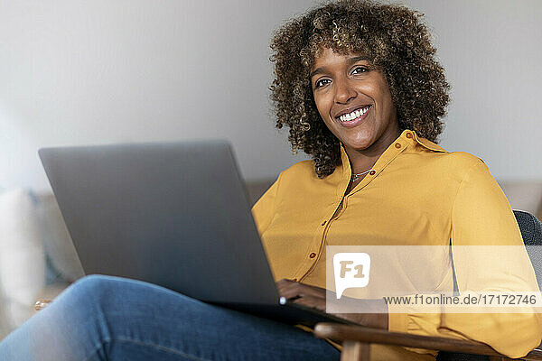 Mid adult woman with laptop looking away while sitting at home