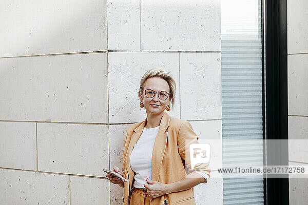 Smiling female entrepreneur with smart phone while standing against wall
