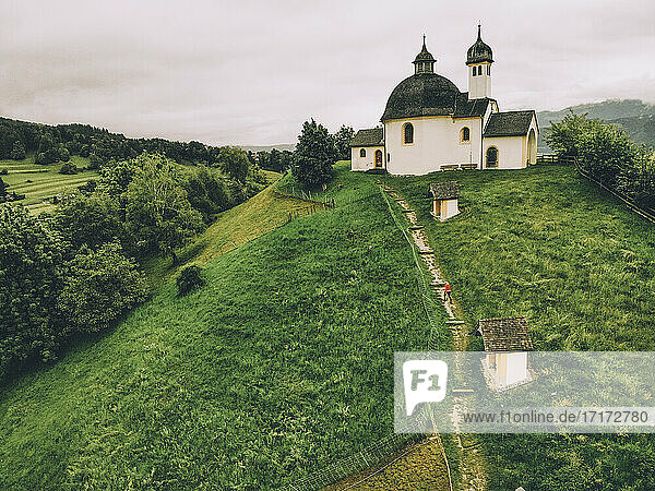 Aerial view of woman walking on green hill towards chapel