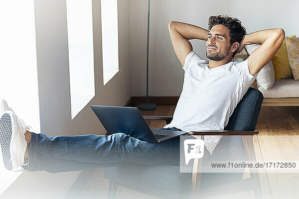 Man with hands behind head relaxing while sitting on armchair at home