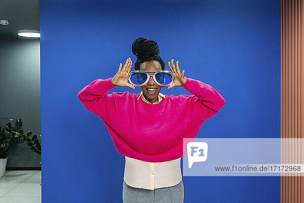 Fröhliche kreative weibliche Fachkraft mit übergroßer Sonnenbrille vor blauer Wand am Arbeitsplatz Fröhliche kreative weibliche Fachkraft mit übergroßer Sonnenbrille vor blauer Wand am Arbeitsplatz