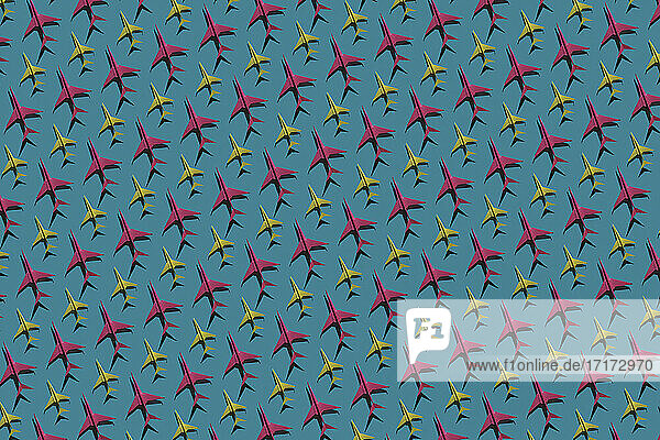 Pattern of pink and yellow origami airplanes