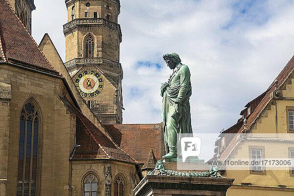 Germany  Baden-Wurttemberg  Stuttgart  Statue of Friedrich Schiller at Schillerplatz with bell tower of Stiftskirche in background