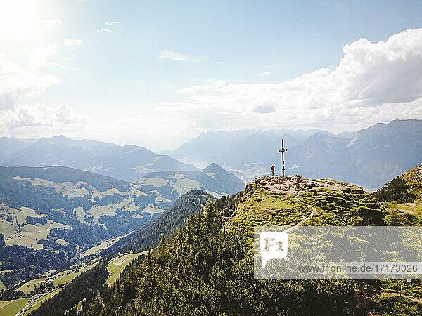 Drone shot of woman standing on mountain peak against sky during sunny day