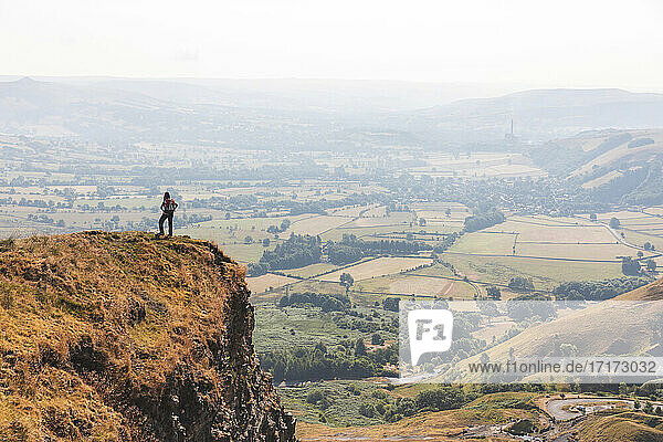 Female explorer standing at edge of mountain cliff on sunny day
