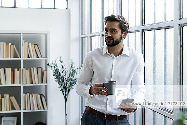 Smiling businessman with mobile phone holding coffee cup while looking away in office