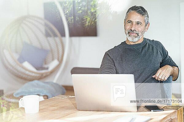 Nachdenklicher Geschäftsmann  der mit seinem Laptop im Büro zu Hause sitzt und wegschaut Nachdenklicher Geschäftsmann, der mit seinem Laptop im Büro zu Hause sitzt und wegschaut
