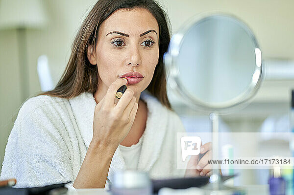 Beautiful woman applying lipstick while looking in mirror at home