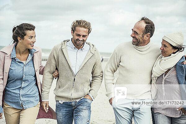 Group of adult friends walking side by side along sandy beach
