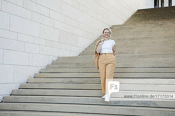 Mature businesswoman with hand in pocket moving down staircase