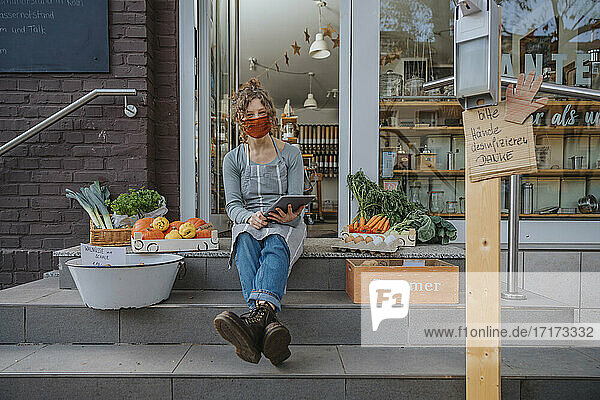 Young female owner with digital tablet sitting on staircase against organic store during COVID-19
