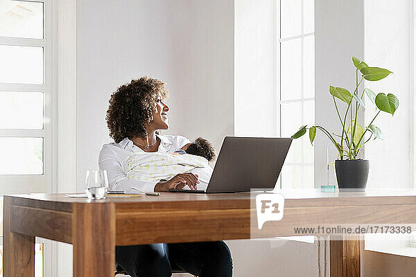 Woman with baby looking through window while sitting at home office