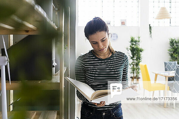 Female professional reading book while standing by bookshelf in office