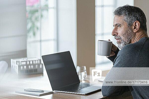 Älterer Geschäftsmann trinkt Kaffee  während er im Büro zu Hause sitzt Älterer Geschäftsmann trinkt Kaffee, während er im Büro zu Hause sitzt