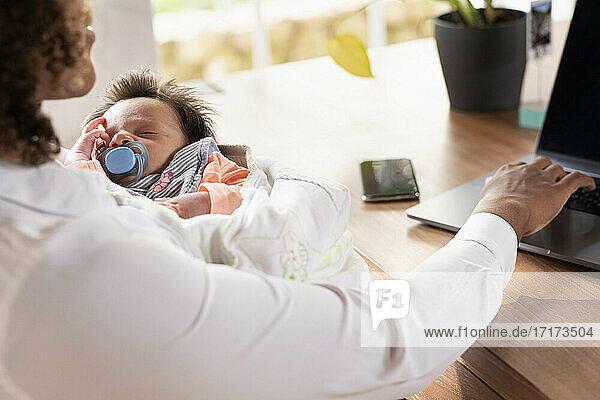 Mutter hält schlafendes Baby  während sie zu Hause am Laptop arbeitet Mutter hält schlafendes Baby, während sie zu Hause am Laptop arbeitet