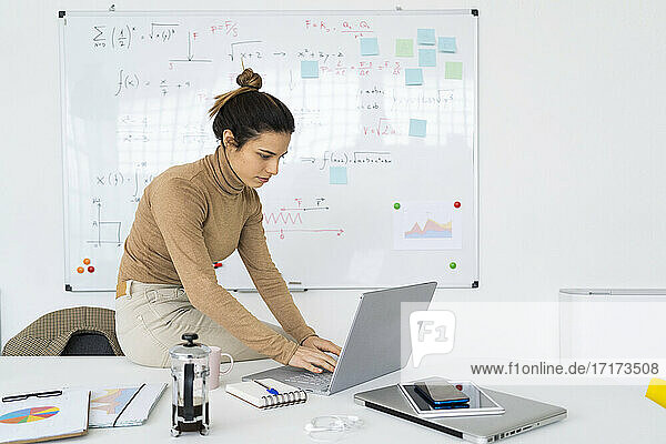Young female student using laptop while doing math