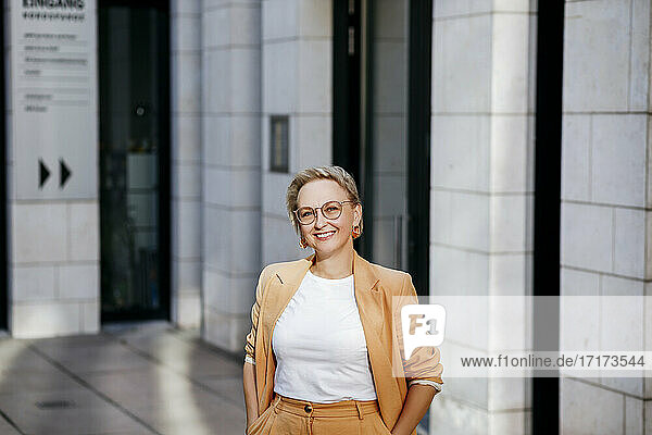 Smiling businesswoman with hands in pockets standing against office building