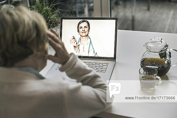 Senior woman taking advice from female doctor through video call in living room