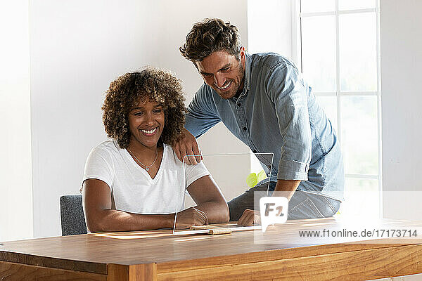 Mid adult couple smiling over transparent screen while sitting at home Mid adult couple smiling over transparent screen while sitting at home