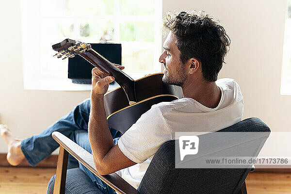 Smiling man playing guitar while relaxing on armchair at home