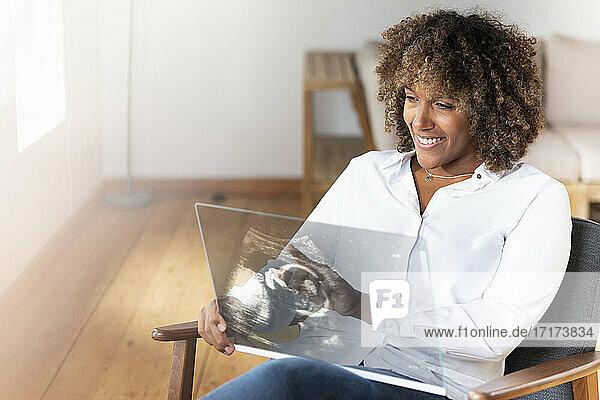 Lächelnde Frau  die zu Hause auf einem Sessel sitzend über einen transparenten Projektionsschirm Ultraschalluntersuchungen durchführt Lächelnde Frau, die zu Hause auf einem Sessel sitzend über einen transparenten Projektionsschirm Ultraschalluntersuchungen durchführt