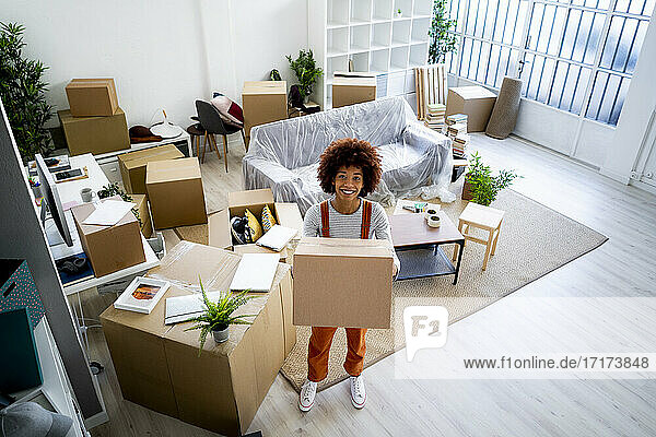 Happy young Afro woman carrying carton while moving in new home