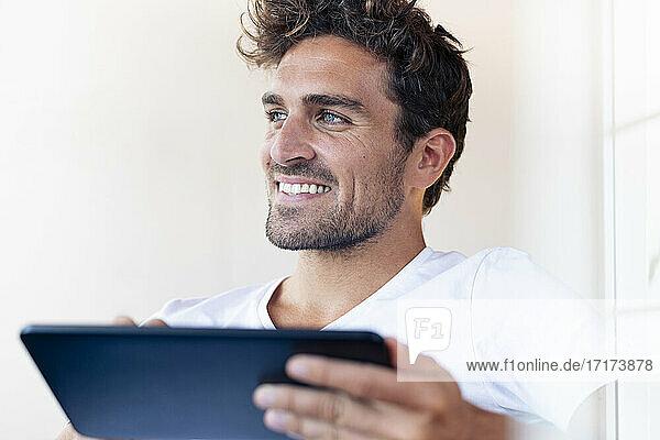 Lächelnder Mann mit digitalem Tablet  der wegschaut  während er zu Hause sitzt Lächelnder Mann mit digitalem Tablet, der wegschaut, während er zu Hause sitzt
