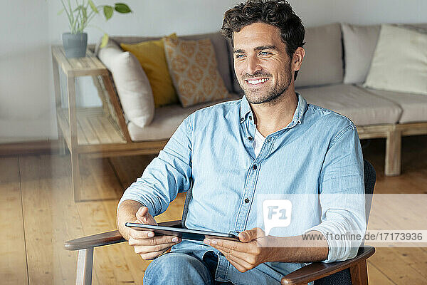 Smiling man with digital tablet looking away while sitting on armchair at home