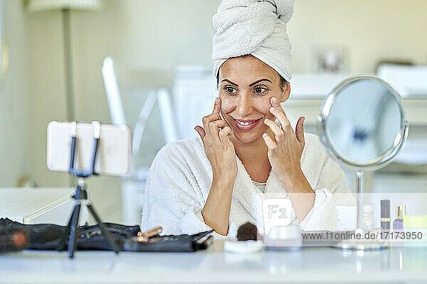 Lächelnde Influencerin trägt Gesichtscreme auf ihr Gesicht auf  während sie zu Hause über ihr Handy bloggt Lächelnde Influencerin trägt Gesichtscreme auf ihr Gesicht auf, während sie zu Hause über ihr Handy bloggt