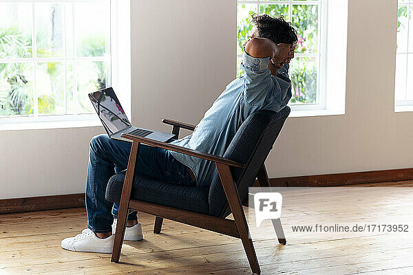Man with hands behind head resting while sitting on armchair at home