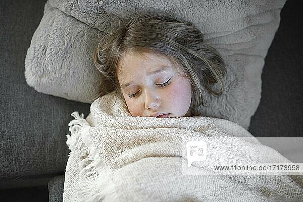 Krankes Mädchen schläft mit Decke auf Sofa zu Hause