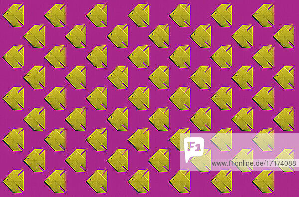 Pattern of yellow origami fish against pink background