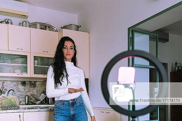 Young woman making video  using ring light and phone