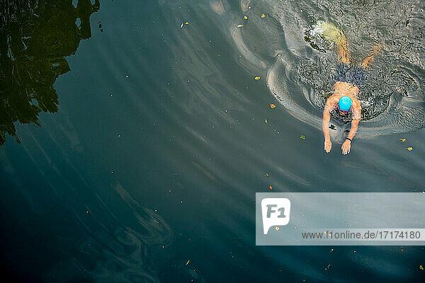 Man wild swimming in river  overhead view  River Wey  Surrey  UK